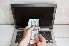 La mano masculina puso bankmotes del dólar en la pantalla del ordenador portátil Fotografía de archivo libre de regalías