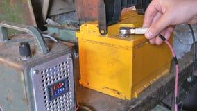La mano masculina separa los terminales a las baterías del ` s del coche para cargar Lecturas y amperímetro del voltímetro almacen de video