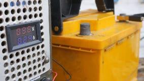 La mano masculina separa los terminales a las baterías del ` s del coche para cargar Lecturas y amperímetro del voltímetro almacen de metraje de vídeo