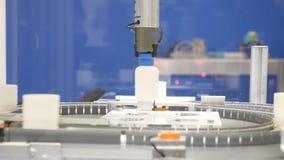 La mano mecánica mueve una botella plástica, un transportador, una banda transportadora, una fábrica, una producción
