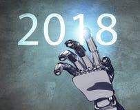 La mano metálica del robot toca la fecha del Año Nuevo 2018 Fotografía de archivo