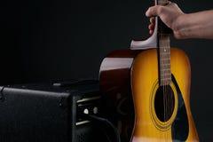 La mano mette la chitarra classica acustica all'amplificatore combinato fotografia stock libera da diritti