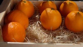 La mano mette l'arancia succosa matura in una scatola di legno archivi video