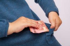 La mano mette la banconota dell'euro dieci in sua tasca Fotografia Stock