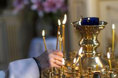 La mano mette una candela per salute nella chiesa Immagini Stock Libere da Diritti