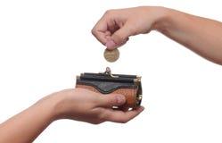 La mano mette una moneta nella borsa Immagini Stock Libere da Diritti