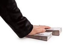 La mano miente encima de dos paquetes de dinero Fotos de archivo libres de regalías