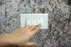 La mano mojada da vuelta en el interruptor eléctrico de las luces en el fondo de madera de la pared imagen de archivo