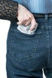 La mano nasconde i dollari in sua tasca Fotografie Stock Libere da Diritti