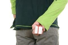 La mano oculta la pequeña parte posterior del regalo detrás Foto de archivo libre de regalías