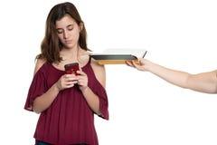 La mano ofrece un libro a un adolescente enviciado a su teléfono foto de archivo