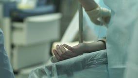 La mano paciente del ` s en la mesa de operaciones metrajes