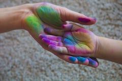 La mano parentale tiene una palma del bambino dipinto con i pastelli colorati Fotografia Stock