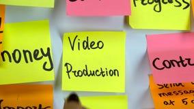 La mano pega una etiqueta engomada con una producción video de la inscripción en un tablero almacen de video