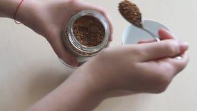 La mano pone la cucharada dos de café instantáneo del tarro de cristal en taza almacen de metraje de vídeo