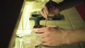 La mano pone il tabacco rosso succoso fragrante nella ciotola del narghilé Preparazione di uno shisha video d archivio