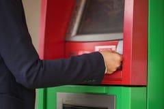 La mano pone la tarjeta de crédito en la atmósfera imagen de archivo