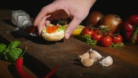 La mano pone un bocadillo con el caviar en un tablero metrajes