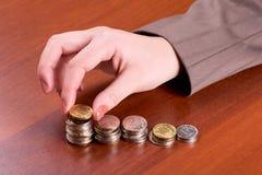 La mano pone una moneda en la pila Fotografía de archivo libre de regalías