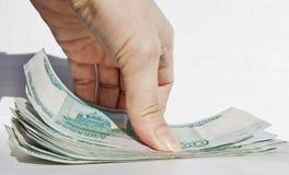 La mano prende dalla superficie della tavola un pacchetto delle banconote da 1000 rubli immagine stock