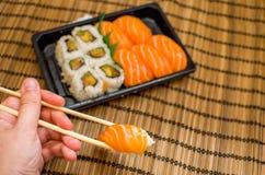 La mano prende il piatto misto dei sushi Immagine Stock Libera da Diritti