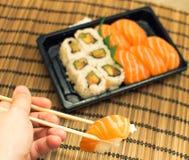 La mano prende il piatto misto dei sushi Fotografia Stock