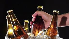 La mano prende una bottiglia della birra fredda Priorità bassa nera Fine in su stock footage