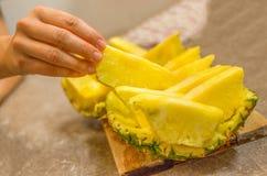 La mano prende una fetta dell'ananas Fotografie Stock Libere da Diritti