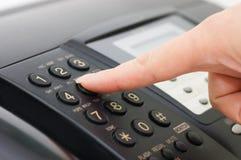 La mano presiona el botón del fax Fotos de archivo