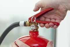 La mano presiona el extintor del disparador Imagen de archivo