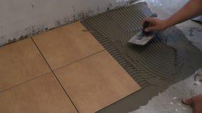 La mano principal pone el pegamento del cemento de la teja en piso Diríjase la renovación metrajes