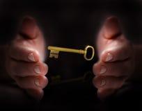 La mano protegge la chiave dorata Fotografie Stock
