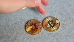 La mano puso Bitcoin de oro en el fondo gris, concepto del cryptocurrency almacen de metraje de vídeo
