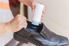 La mano puso el polvo a un zapato, parada del olor imagen de archivo libre de regalías