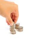 La mano puso la moneda al dinero Foto de archivo libre de regalías