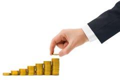 La mano puso la moneda a la escalera del dinero Imagen de archivo libre de regalías