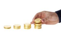 La mano puso monedas en la pila de monedas Imagen de archivo libre de regalías