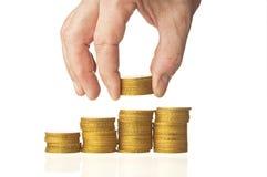 La mano puso monedas a la pila Imágenes de archivo libres de regalías