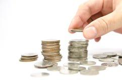 La mano puso monedas a la pila de monedas Imagen de archivo libre de regalías