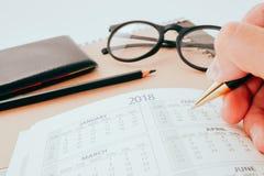 La mano que escribe el cuaderno en blanco del planeamiento en el escritorio nos utiliza vida del horario del organizador o concep Foto de archivo