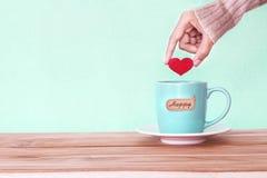 la mano que llevaba a cabo forma roja del corazón puso en una taza de la taza de café con el hap Foto de archivo