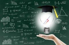 La mano que sostiene la bombilla con la certificación para la graduación muestra el conocimiento de la ingeniosidad Fotografía de archivo