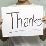 La mano que sostiene el papel escribe palabra de las gracias Imagen de archivo libre de regalías