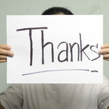 La mano que sostiene el papel escribe palabra de las gracias Fotografía de archivo
