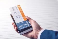 La mano que sostiene el teléfono con los boletos de tren Concepto de compra en línea y reservación de los boletos para el viaje Fotos de archivo