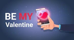 La mano que sostiene el teléfono elegante con sea mi invitación de la celebración de Valentine Text Message Love Holiday Fotos de archivo