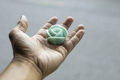 La mano que sostiene el verde de la flor del postre o el caramelo tailandés de Aalaw foto de archivo