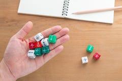 La mano que sostiene la fracción del color corta en cuadritos Imágenes de archivo libres de regalías