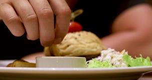 La mano que sostiene las patatas fritas serradas sumerge a la salsa de tomate almacen de video