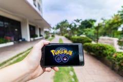 La mano que sostiene un teléfono móvil que juega Pokemon va imagen de archivo